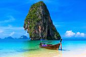 Summer beach tropical landscape. Thailand island scenic background, azure water, traditional long tail boat and rock