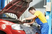 One young auto mechanic tighten screw with spanner during automobile car maintenance at engine auto