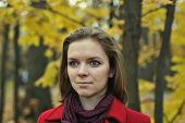 Portrait of cute girl in a red coat in the autumn park