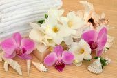 Orchid and fresia flower spa arrangement with natural soap, shells and white towels over bamboo background.
