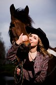 Lovely Blond Woman In A Hat Standing By Horse