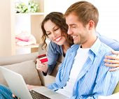 Online Shopping. Happy Smiling Couple Using Credit Card to Internet Shop. Young couple with laptop a