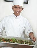stock photo of chafing  - smiling chef holding food on chafing dish for buffet - JPG