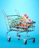 shopping trolley with pills, on blue background