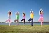 People in group  practice Yoga asana on lakeside. Yoga concept.