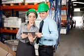 Two young supervisors in formalwear using digital tablet at warehouse