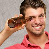 man looking inside an empty bottle, indoor