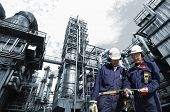 stock photo of gas-pipes  - refinery engineers with large industry in background - JPG