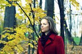 Girl in a red coat in the autumn park (crossprocess)