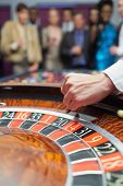 pic of roulette table  - Dealer dropping ball into roulette wheel in casino - JPG