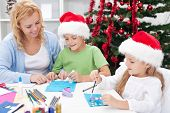 Family around christmas time making greeting cards wearing santa hats