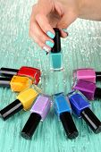 Beautiful woman hands with blue manicure and several bottles with nail polish, on color background