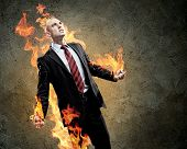 Image of young businessman in anger burning fire