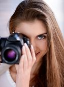 Portrait of beautiful smiling young woman using the DSLR camera