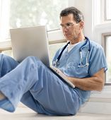 picture of infirmary  - Mature doctor sitting on floor leaning against wall in blue scrubs working on his laptop - JPG