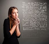 stock photo of anal  - Pretty young woman looking at stock market graphs and symbols - JPG