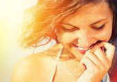 Beauty Sunshine Girl Portrait. Happy Woman Smiling and looking Down. Sunny Summer Day under the Hot Sun on the Beach.