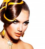 Fashion Model Girl Portrait with Yellow and Orange Makeup and Earrings. Creative Hairstyle. Hairdo.