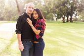 Happy young couple portrait, asian woman, caucasian man, hugging tenderly in a nice park