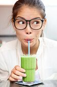 Green vegetable smoothie juice - woman hipster drinking smoothie as part of healthy eating lifestyle. Cute funny face expression looking sideways. Beautiful young mixed race Asian Caucasian girl model
