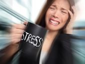 Stress - business person stressed at office. Business woman holding coffee cup with STRESS written. Overworked and over caffeinated female businesswoman.