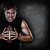 Football player portrait holding american football staring aggressive looking at camera on black cha
