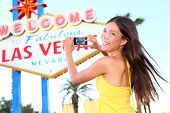 Las Vegas Sign tourist woman happy taking photo picture with smart phone in front of Welcome to Fabu