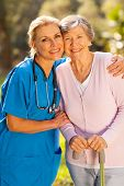 friendly mid age caregiver hugging senior patient outdoors