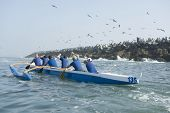 Rear view of multiethnic outrigger canoeing team heading to race stage