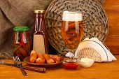 Bier und gegrillten Würstchen auf Holztisch auf Sackleinen-Hintergrund