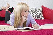 Постер, плакат: Полная длина красивая девочка подросток изучая лежа на кровати