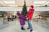 MOSCOW - DEC. 30: Mother and daughter standing near Christmas tree in the hall of the Cultural Center ZIL on December 30, 2012, Moscow, Russia. In December 2012 Centre celebrated its 75th anniversary