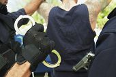 stock photo of caught  - Cropped image of policemen arresting criminal - JPG