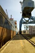 Crane loading a freighter with cargo on quayside at Limassol Cyprus