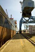 Grúa cargando un carguero con carga en el muelle en Limassol de Chipre