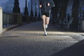 stock photo of hooded sweatshirt  - Lowsection of a man jogging on city pavement at dawn n London - JPG