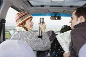 Happy young woman holding flask while looking at man in car during road trip