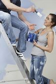 Young couple having fun while painting unrenovated house at stepladder