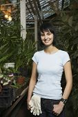 Portrait of young female botanist standing in greenhouse