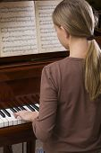 Rear view of a teenage girl playing the piano