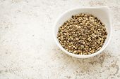 pic of ceramic bowl  - small ceramic bowl of  dry hemp seeds against a ceramic tile background with a copy space - JPG