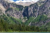 stock photo of avalanche  - Waterfalls stream from the Sperry Glacier and Bearhat Mountain into Avalanche Lake in Glacier National Park Montana - JPG