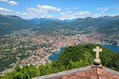 stock photo of salvatore  - Cross on a church rooftop on the top of Mount San Salvatore with mountain panorama landscape view in Lugano Lake Como district at Italian and Swiss border - JPG