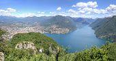Landscape Of Alpine Mountains At Lake Lugano