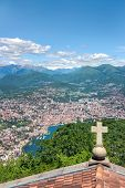 pic of salvatore  - Cross on a church rooftop on the top of Mount San Salvatore with mountain panorama landscape view in Lugano Lake Como district at Italian and Swiss border - JPG