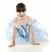 A beautiful elementary girl happily looking at the viewer from the floor in her blue recital dress.  On a white background.