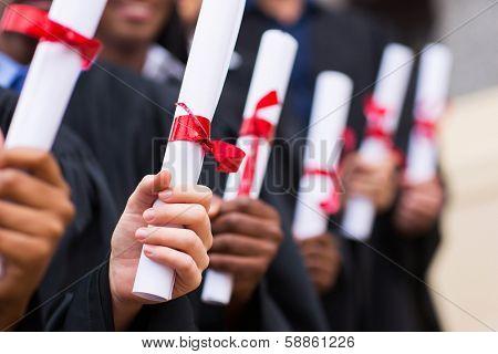 group of multiracial graduates holding diploma poster