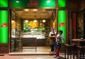 SARAJEVO, BOSNIA AND HERZEGOVINA - AUGUST 13, 2012: Two female workers stand in front of Jami shop at night. Jami is very popular Bosnian food brand.