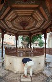 SARAJEVO, BOSNIA AND HERZEGOVINA - AUGUST 13, 2012: Man drinking water from fountain on the the Sadi