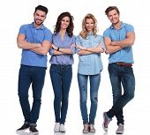 full body picture of four casual young people with hands folded standing on white background and smi